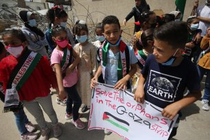Palestinian children protest against Israel's destrution of the central office of Al-Amal Institute for Orphan in Gaza [Mohammed Asad/Middle East Monitor]
