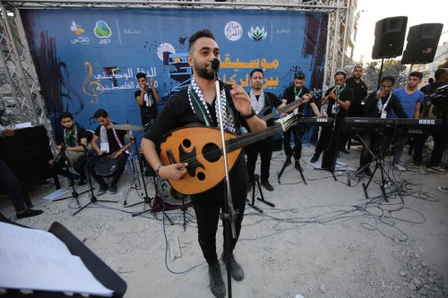 Palestinians in Gaza attend the Music Among the Rubble concert on 28 June 2021 in front of the remains of Al Shuruq Tower [Mohammed Asad/Middle East Monitor]