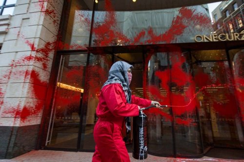Palestine Action activists target the headquarters of LaSalle Investment Management, drenching the site in blood-red paint, preventing entry and covering the site in 'war crime scene' tape, on 9 June 2021 [Pal_action/Twitter]