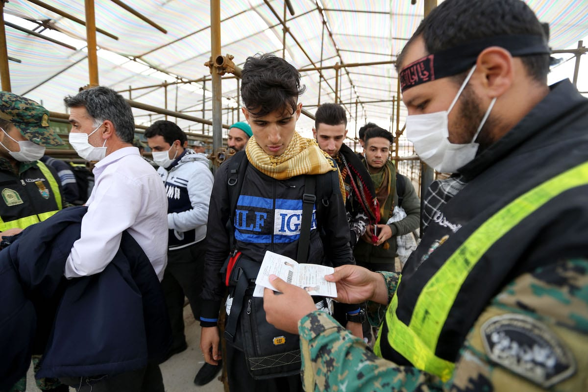 Iranian security forces check the passport of a pilgrim at the Mehran border point between Iran and Iraq, as thousands of Iranian Shiite Muslim pilgrims headed towards the central Iraqi shrine city of Karbala on 27 October 2018 [ATTA KENARE/AFP via Getty Images]