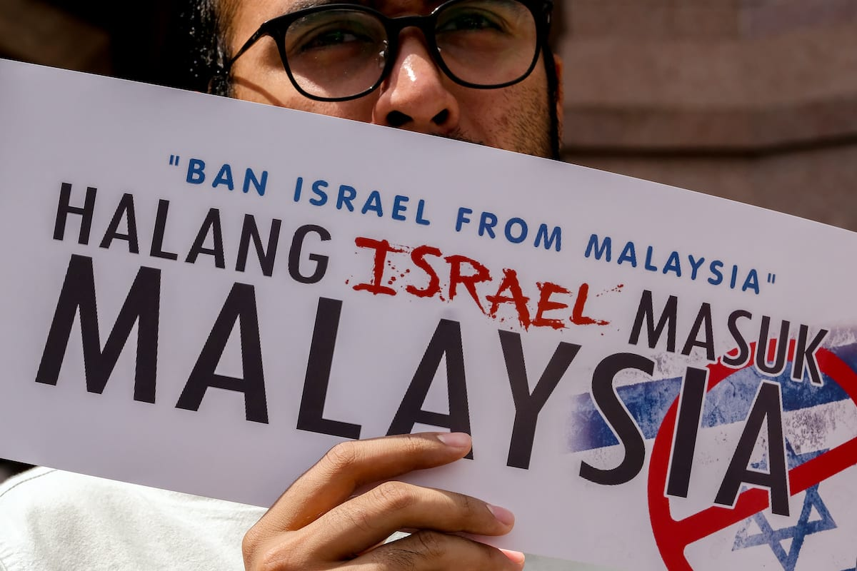 A protestor holds a poster outside the Putra mosque during demonstrations against Israel to enter Malaysia as they support the Malaysia prime minister statement on 1 February 2019 in Putrajaya outside Kuala Lumpur, Malaysia. [Mohd Samsul Mohd Said/Getty Images]