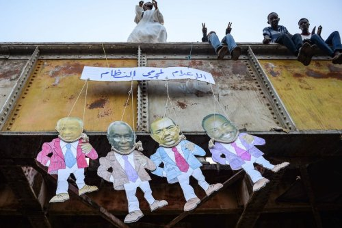 """Sudanese men sit together atop a bridge dangling paper puppets showing the faces of (L to R) former presidential advisor Nafi Ali Nafi, former vice president Ali Osman Taha, ousted president Omar al-Bashir, and former National Congress Party leader Ahmed Haroun, with a sign above them reading in Arabic """"death penalty for the regime criminals"""", during their protest outside the army headquarters in the capital Khartoum on 10 May 2019. [MOHAMED EL-SHAHED/AFP via Getty Images]"""