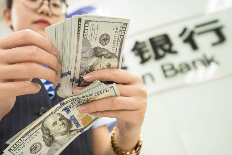 A Chinese bank employee counts US dollar bills at a bank counter in Nantong in China's eastern Jiangsu province on 6 August 2019. [STR/AFP via Getty Images]