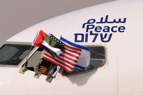"""The Emirati, Israeli and US flags are picture attached to an air-plane of Israel's El Al, adorned with the word """"peace"""" in Arabic, English and Hebrew, upon it's arrival at the Abu Dhabi airport in the first-ever commercial flight from Israel to the UAE, on August 31, 2020 [KARIM SAHIB/AFP via Getty Images]"""