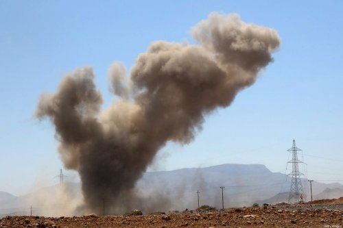 """A smoke plume rises following an explosion as forces loyal to Yemen's Saudi-backed government clash with Houthi fighters around the strategic government-held """"Mas Camp"""" military base, in al-Jadaan, Yemen, on November 22, 2020 [-/AFP via Getty Images]"""