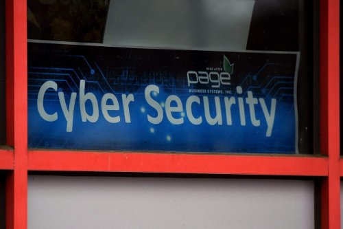 A 'Cyber Security' sign is displayed in the window of a computer store on December 18, 2020 [OLIVIER DOULIERY/AFP via Getty Images]