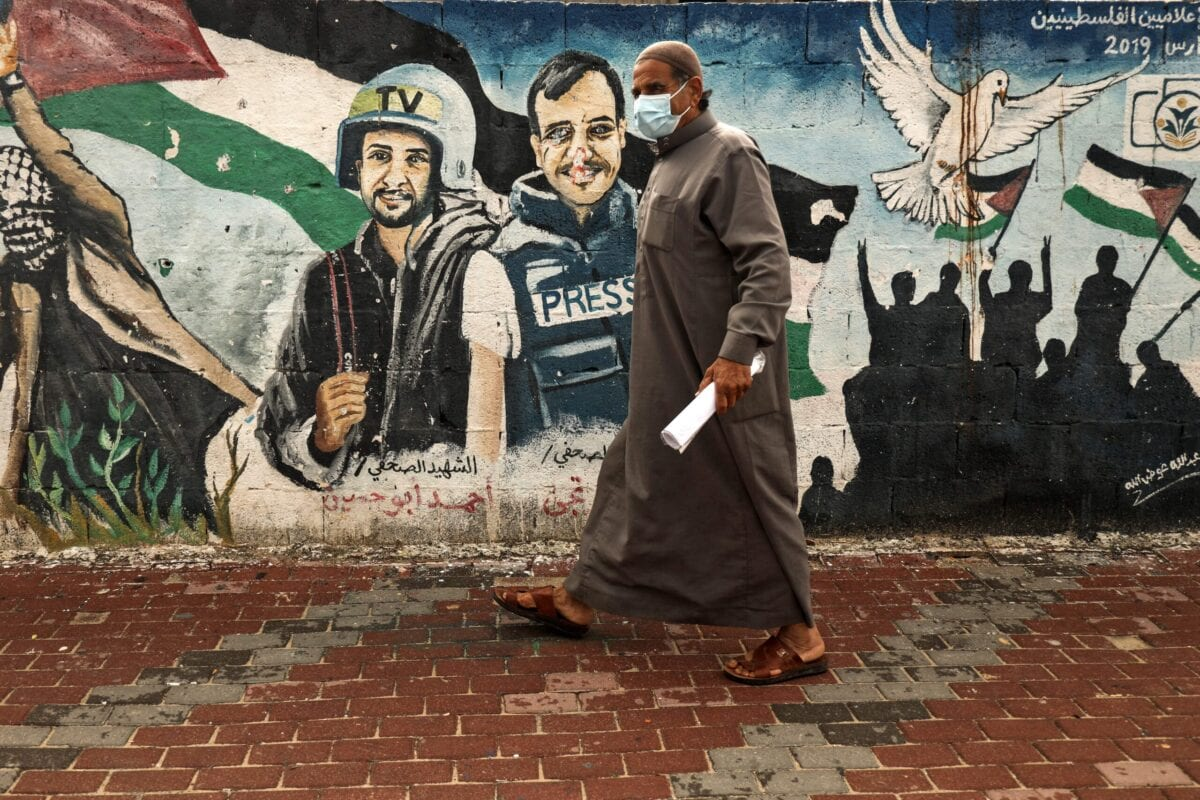 A Palestinian man wearing a face mask walks past a mural of journalists killed in the 2014 between Hamas and Israel, in Gaza City, on March 4, 2021 [MOHAMMED ABED/AFP via Getty Images]
