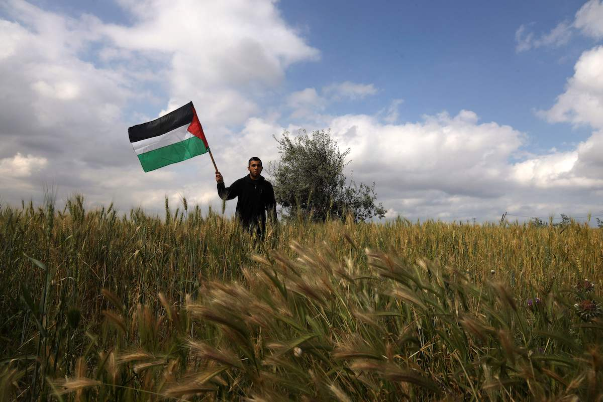 A Palestinian man waves a national flag near the border with Israel, east of Gaza City on 30 March 2021. [MOHAMMED ABED/AFP via Getty Images]