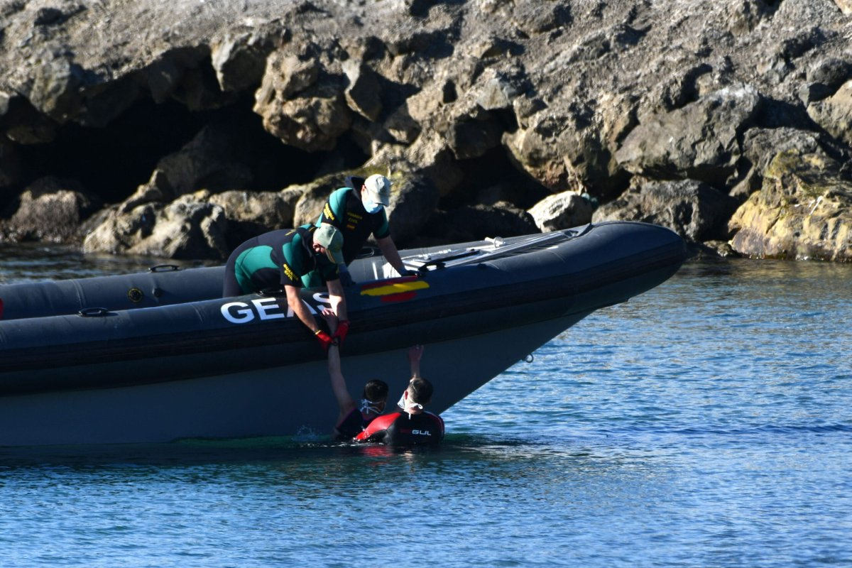 Spanish Civil guards pull a migrant into an inflatable boat after he arrived swimming to the Spanish enclave of Ceuta from neighbouring Morocco on 17 May 2021 [ANTONIO SEMPERE/AFP/Getty Images]