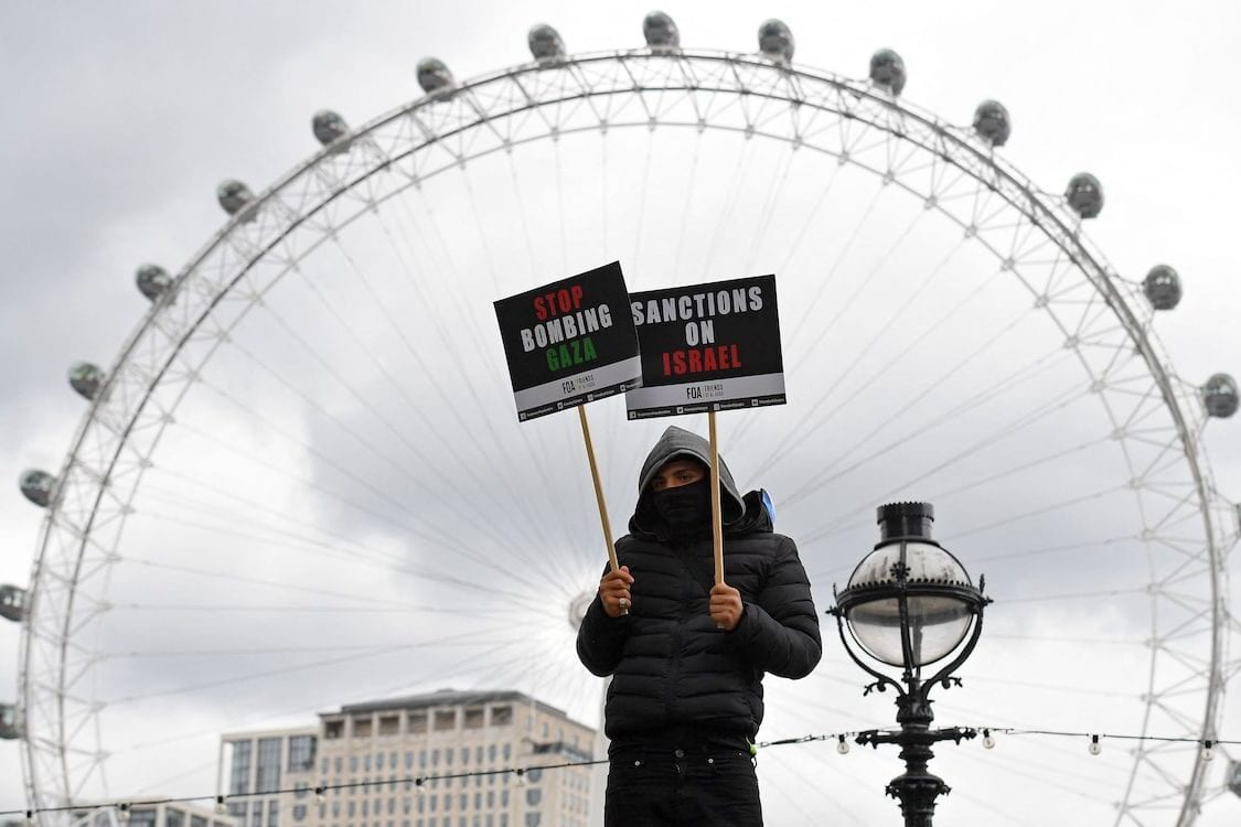 A pro-Palestine activist holds a placards opposite the London Eye as they march in central London on 22 May 2021. [JUSTIN TALLIS/AFP via Getty Images]