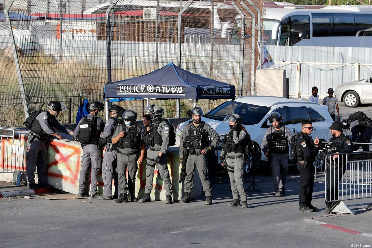 Israeli security forces stand guard to prevent Palestinians from passing through an Israeli checkpoint at the entrance of the Sheikh Jarrah neighbourhood in east Jerusalem, during a protest by demonstrators demanding the reopening of the roadblock, on May 29, 2021 [AHMAD GHARABLI/AFP via Getty Images]