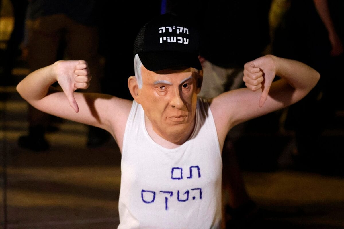 """An Israeli protester wears a mask of Prime Minister Benjamin Netanyahu and a T-shirt with a slogan reading in Hebrew: """"the ceremony is over"""" on May 31, 2021 in Tel Aviv [JACK GUEZ/AFP via Getty Images]"""