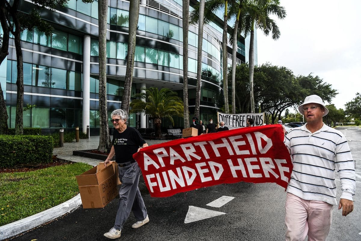 Members of Jewish Voice for Peace hold flags and placards as they protest outside the Duty Free Americas Headquarters in Hollywood, Florida on 2 June 2021. [CHANDAN KHANNA/AFP via Getty Images]