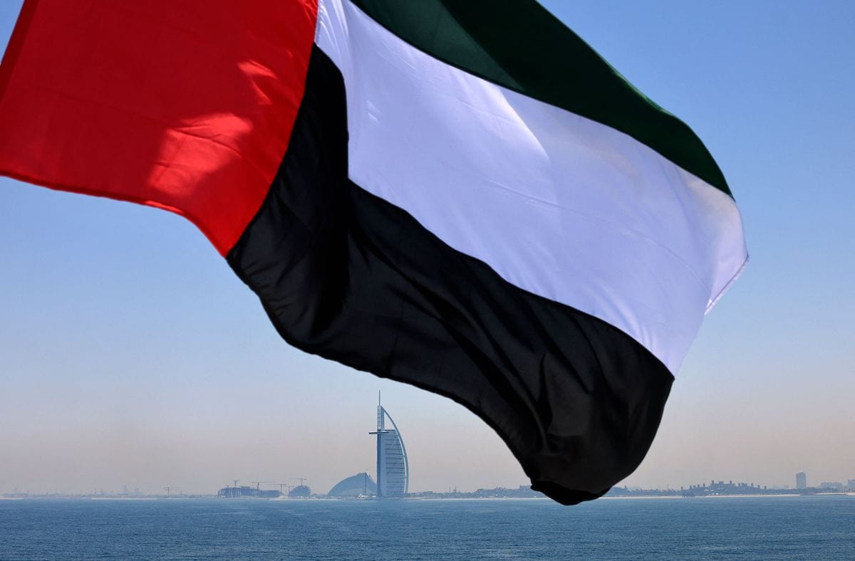 An Emirati flag fluttering above Dubai's marina with the Burj Al Arab landmark hotel (C) in the background, 3 June 2021 [KARIM SAHIB/AFP via Getty Images]
