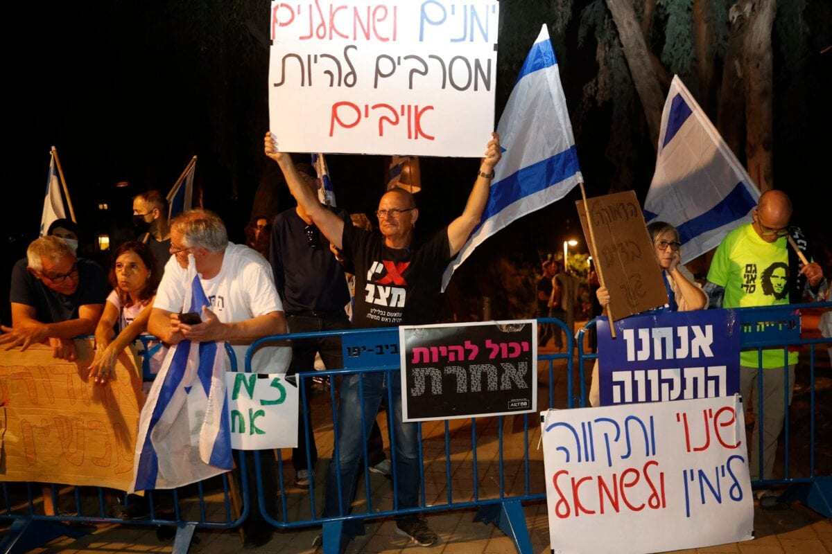 """Supporters of Israeli """"change coalition"""" carry placards and wave the national flag during a demonstration in support of the coalition to form a government, in the Israeli city of Tel Aviv, on June 3, 2021 [JACK GUEZ/AFP via Getty Images]"""