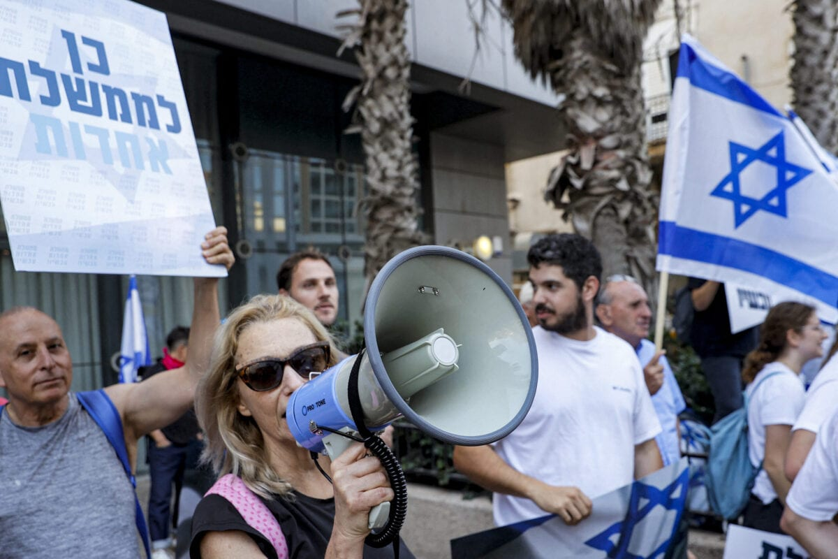 """A supporter of Israel's newly-formed government """"change coalition"""" uses a megaphone as others wave Israeli flags during a rally in support of the coalition in the Israeli city of Tel Aviv, on June 6, 2021 [JACK GUEZ/AFP via Getty Images]"""
