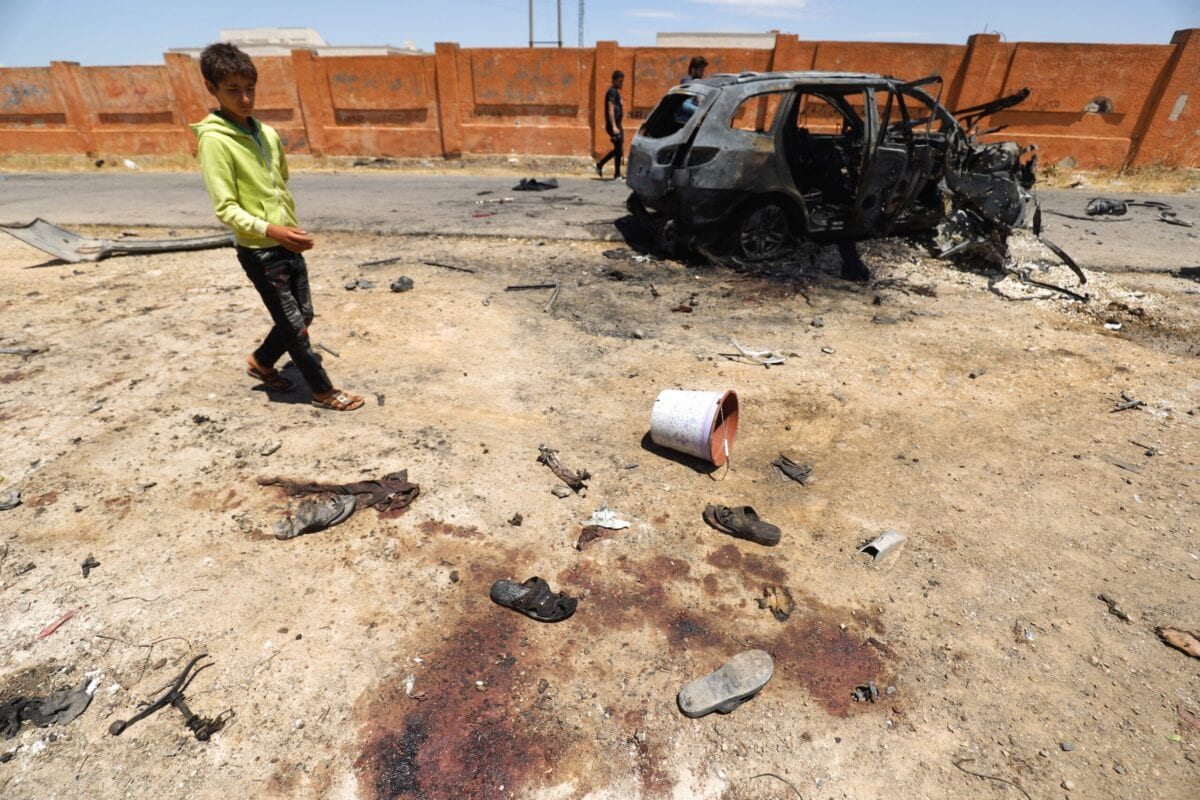 A Syrian boy looks at blood stains and shoes left behind next to a charred car, hit in reported bombardment by government forces on the village of Iblin in the Jabal al-Zawiya region in Syria's rebel-held northwestern Idlib province, on June 10, 2021 [ABDULAZIZ KETAZ/AFP via Getty Images]