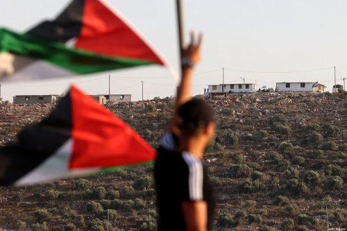 Palestinian flags flutter towards a new Israeli settler outpost in the village of Beita, south of Nablus in the occupied West Bank, on 13 June 2021 [JAAFAR ASHTIYEH/AFP/Getty Images]