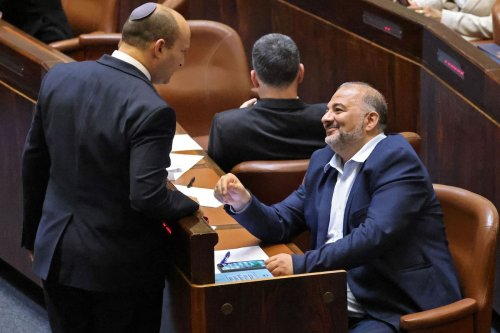 Head of Israel's right-wing Yamina party Naftali Bennett (L) chats with Mansour Abbas, head of the conservative Islamic Raam party during a special session to vote on a new government at the Knesset in Jerusalem, on 13 June 2021. [EMMANUEL DUNAND/AFP via Getty Images]