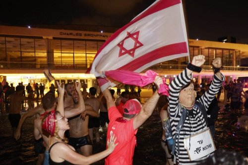 Israeli celebrate the passing of a Knesset vote confirming a new coalition government during a rally in Rabin Square in the Mediterranean coastal city of Tel Aviv on June 13, 2021 [JACK GUEZ/AFP via Getty Images]