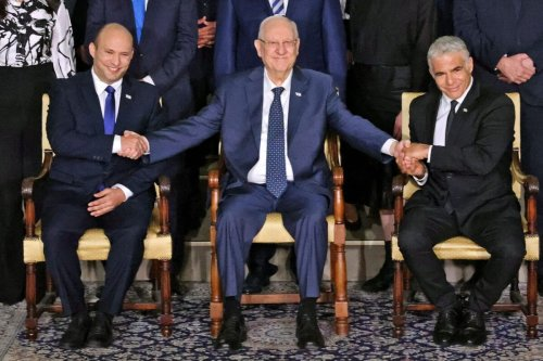Outgoing Israeli President Reuvin Rivlin (C) is flanked by Prime Minister Naftali Bennett (L) and alternate Prime Minister and Foreign Minister Yair Lapid during a photo with the new coalition government, at the President's residence in Jerusalem, on June 14, 2021 [EMMANUEL DUNAND/AFP via Getty Images]