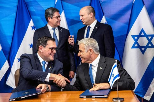 Israeli Foreign Minister Yair Lapid (bottom R) shakes hands with Honduran Foreign Minister Lisandro (bottom L) as Israeli Prime Minister Naftali Bennett (top R) speaks with Honduran President Juan Orlando Hernandez (top L) during the signing of bilateral agreements at the Prime Minister's Office in Jerusalem on 24 June 2021. [HEIDI LEVINE/AFP via Getty Images]