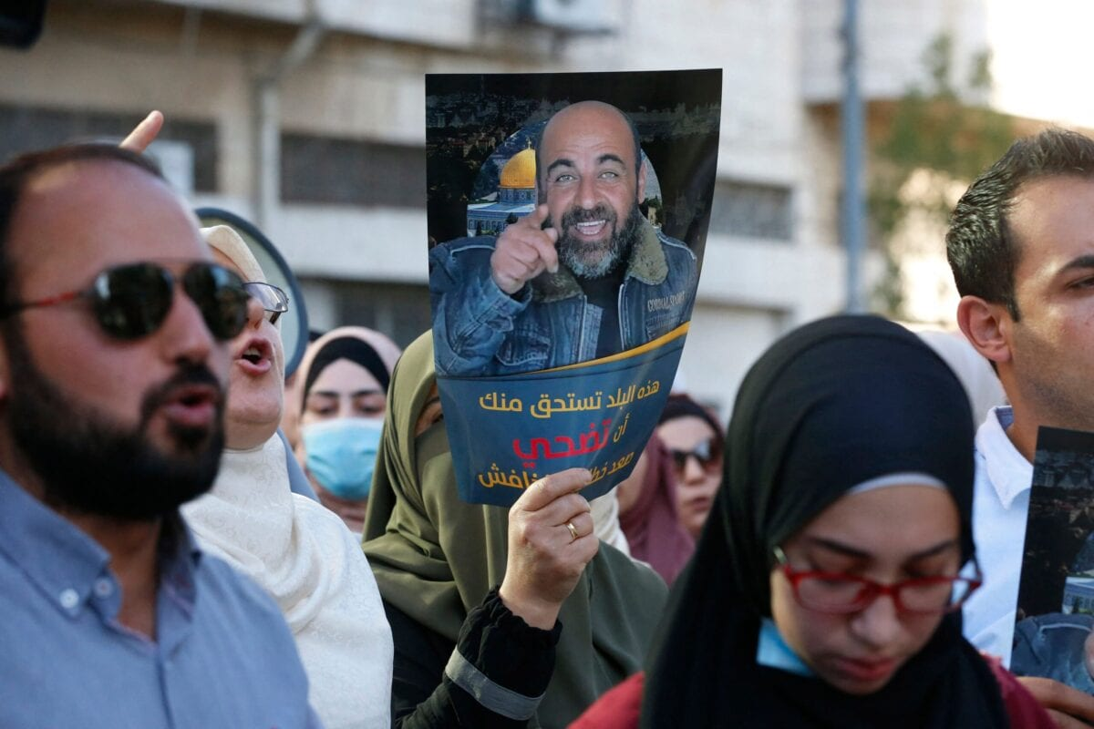 Palestinians hold posters depicting human rights activist Nizar Banat during a protest triggered by the violent arrest and death in custody of Banat, in his hometown of Hebron in the occupied West Bank, on June 27, 2021 [MOSAB SHAWER/AFP via Getty Images]