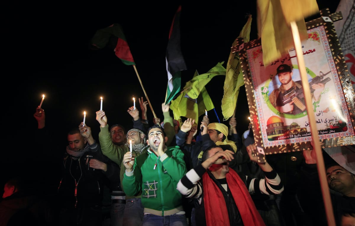 Palestinians celebrate as they wait for the release of Palestinian prisoners in Rafah, crossing in southern Gaza strip, on December 18, 2011. Israel released 550 Palestinian prisoners to complete a swap deal which brought about the release of captive soldier Gilad Shalit. [MAHMUD HAMS/AFP via Getty Images]
