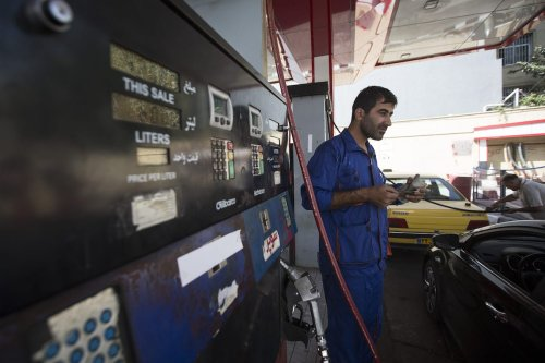 A petrol attendant holds a wad of rial banknotes as he serves customers at a gas station operated by the National Iranian Oil Co. in Tehran, Iran, on 24 Aug. 2015. [Simon Dawson/Bloomberg via Getty Images]