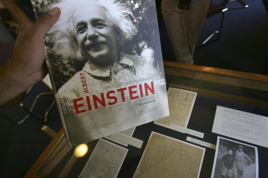 A journalist picks up a book on Albert Einstein during a press conference displaying newly-revealed letters and photos from the Albert Einstein archive, at the Hebrew University July 10, 2006 in Jerusalem. [David Silverman/Getty Images]