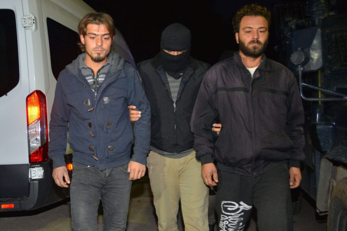 A masked Turkish special force police officer detains two men during a house raid to arrest suspected members of Daesh in Adana, on November 10, 2017 [DOGAN NEWS AGENCY/AFP via Getty Images]
