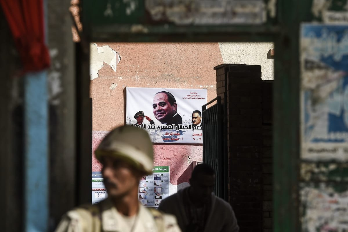 """An Egyptian army conscript stands guard outside a polling station before the start of the first day of the 2018 presidential elections, in Boulaq al-Dakrour neighbourhood in the capital Cairo's southwestern Giza district on 26 March 2018, with an electoral poster seen behind inside the station depicting incumbent President Abdel Fattah al-Sisi (C) between late Presidents Anwar Sadat (L) and Gamal Abdel Nasser (R) with a caption reading in Arabic """"Support the Egyptian Army against terrorism"""". [KHALED DESOUKI/AFP via Getty Images]"""
