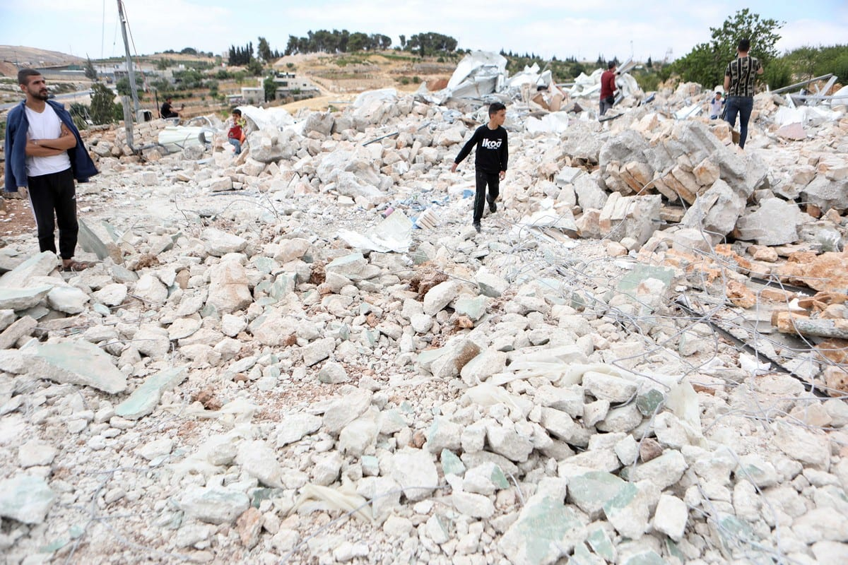 Palestinians collect their usable wares from ruins after Israeli forces demolished their house in the West Bank on 17 June 2021 [Mamoun Wazwaz/Anadolu Agency]