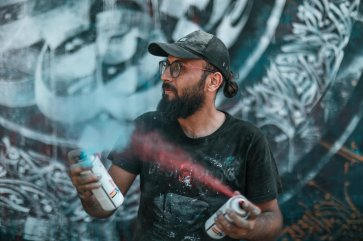 Belal Khaled works on his next piece of art in July 2021 [Majdi Fathi]