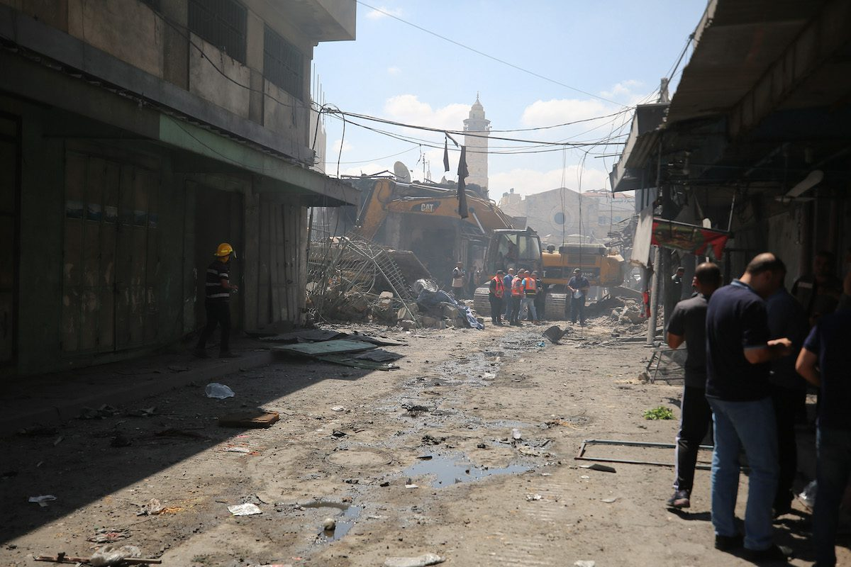 Civil right defense members conduct debris work at the scene after an explosion in a building at Al-Zawiya market in Gaza City, Gaza on July 22, 2021. [Mustafa Hassona - Anadolu Agency]