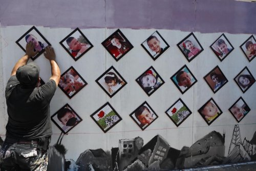 Pictures of Palestinian children killed in the Israeli attack on Gaza in May 2021 are placed outside the UNDP office on 13 July 2021 [Mohammed Asad/Middle East Monitor]