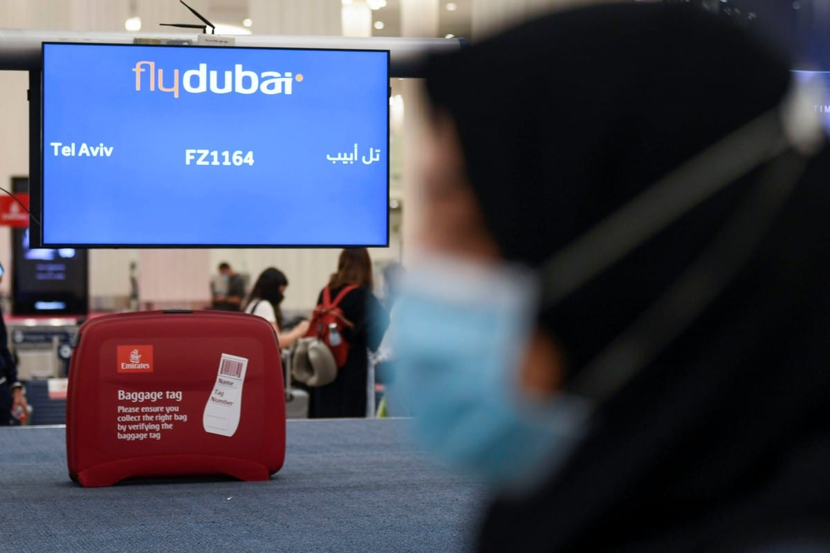 A woman walks past luggage pick-up for arrivals in the UAE on 26 November 2020 [KARIM SAHIB/AFP/Getty Images]