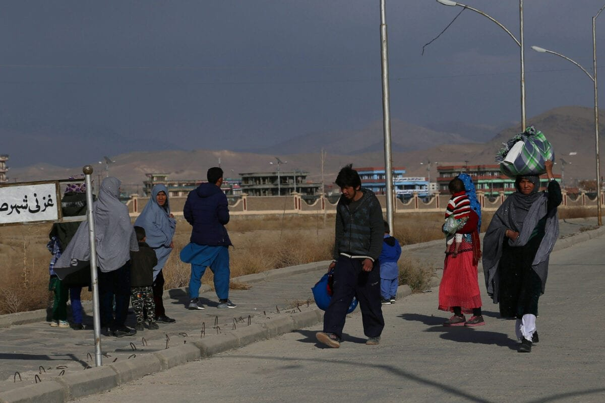 An internally displaced Afghan family walks with their belongings after fleeing from Jaghori district to escape ongoing battles between Taliban and Afghan security forces, in Ghazni on November 13, 2018 [ZAKERIA HASHIMI/AFP via Getty Images]