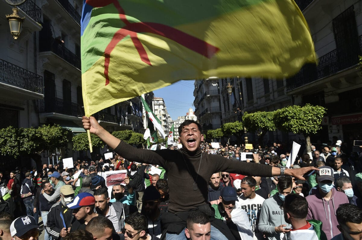 An Algerian anti-government demonstrator waves an Amazigh (Berber) flag during a protest in the capital Algiers, on March 12, 2021 [RYAD KRAMDI/AFP via Getty Images]