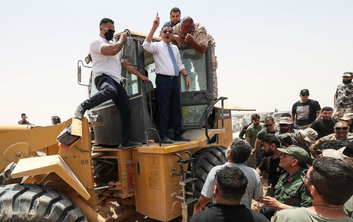 Libyan Interim Prime Minister Abdulhamid Dbeibah, waves as he stands atop an excavator on June 20, 2021, in the town of Buwairat al-Hassoun, during a ceremony to mark the reopening of 300-kilometre road between the cities of Misrata and Sirte. [MAHMUD TURKIA/AFP via Getty Images]
