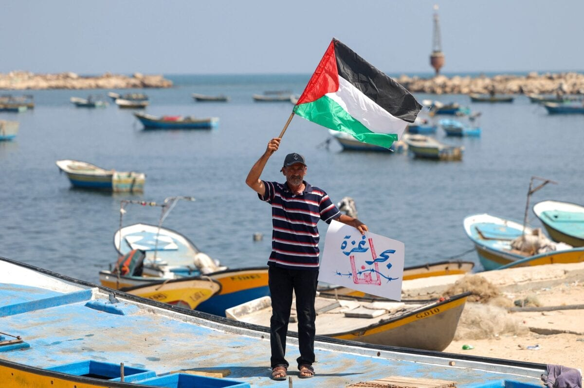 A Palestinian fisherman waves a Palestinian flag during a protest against the blockade on Gaza at the port of Gaza City on July 11, 2021 [SAID KHATIB/AFP via Getty Images]