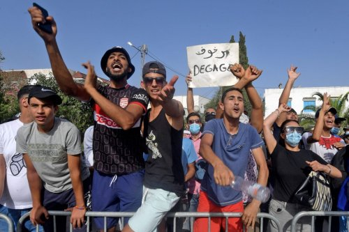Supporters of Tunisia's President Kais Saied chant slogans denouncing the country's main Islamist Ennahda (Ennahdha) party in front of the Parliament which was cordoned-off by the military in the capital Tunis on 26 July 2021 [FETHI BELAID/AFP via Getty Images]