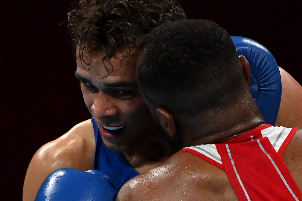 Morocco's Youness Baalla (red) and New Zealand's David Nyika fight during their men's heavy (81-91kg) preliminaries round of 16 boxing match during the Tokyo 2020 Olympic Games at the Kokugikan Arena in Tokyo on 27 July 2021. [LUIS ROBAYO/AFP via Getty Images]