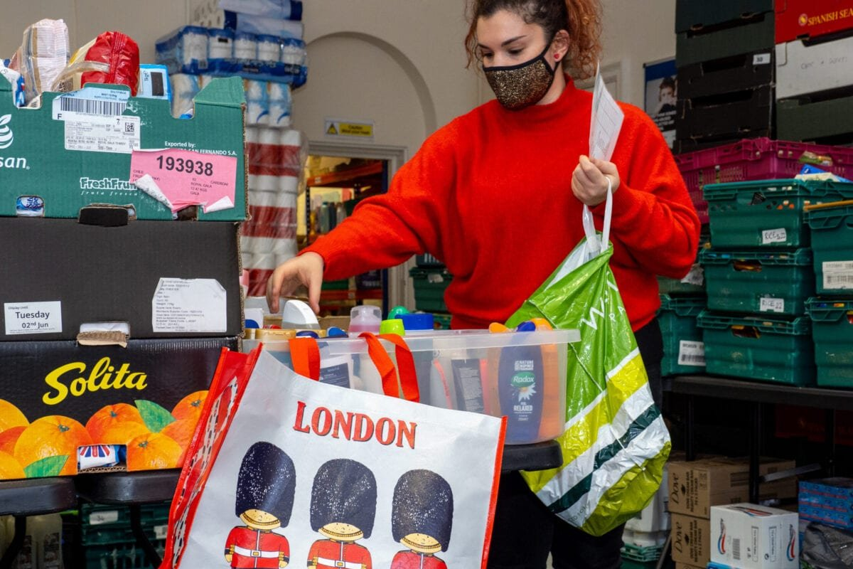 A volunteer packs and prepares food parcels at the Tottenham food bank at Tottenham Town Hall on January 21 ,2021 in London, England [Peter Dench/Getty Images]