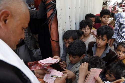 A volunteer checks cards of children, from families who were affected by the war and blockade, before they receive free lunch meals, provided by a charitable kitchen at Mseek area on June 29, 2021 in Sana'a, Yemen [Mohammed Hamoud/Getty Images]