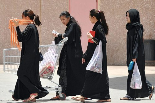 Filipina maids carry shopping bags as they walk out of a mall in Riyadh, on June 12, 2013 [FAYEZ NURELDINE/AFP via Getty Images]