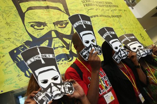Delegates at a meeting of Amnesty International hold up masks depicting ancient Egyptian Queen Nefertiti wearing a gas mask in protest against the ongoing violence as well as sexual violence against women in Egypt on August 19, 2013 in Berlin, Germany [Sean Gallup/Getty Images]