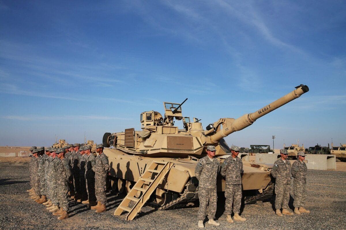 US troops stand to attention next to an Abrams tank on December 8, 2014 [MARK WILSON/AFP via Getty Images]