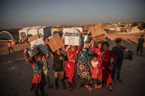 Syrians taking shelter in a camp await for help as they also demand Bab Al-Hawa border crossing to remain open in order to receive any humanitarian aid in Idlib, Syria on June 30, 2021 [Muhammed Said/Anadolu Agency]