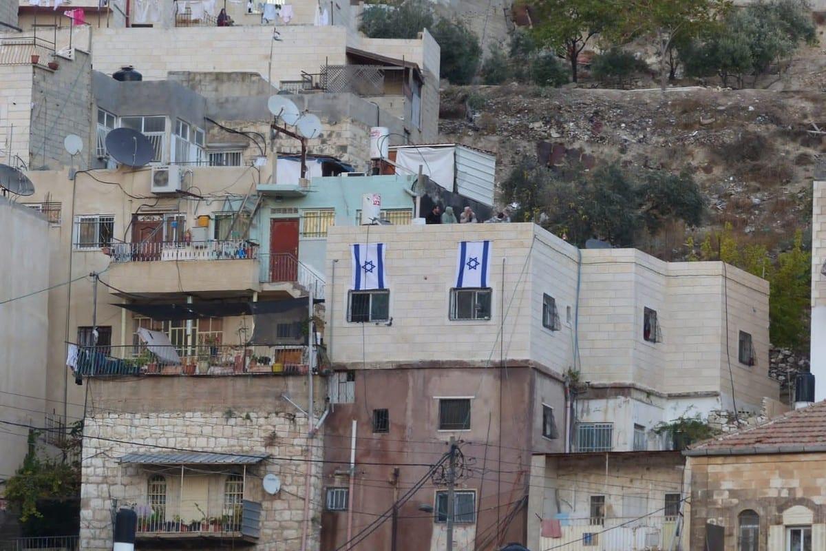 Israeli settlers drape the Israeli flag over a Palestinian residential building in occupied East Jerusalem's Silwan, 2 July 2021